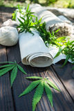 Leaves of cannabis and hemp cloth rollon the dark wooden surface Royalty Free Stock Image