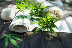 Leaves of cannabis and hemp cloth rollon the dark wooden surface stock photography