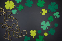 Leaves of clover and golden beads on chalkboard. St. Patricks Day Royalty Free Stock Photography