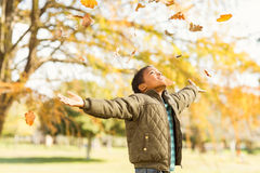 leaves drop onto a little boy with outstretched arms Stock Image