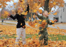 Leaves falling on children Royalty Free Stock Images