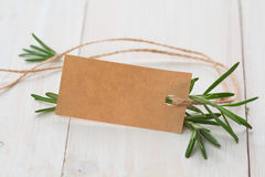 Leaves of fresh rosemary with blank tag. On wooden background Royalty Free Stock Photos