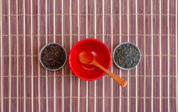 Leaves of green tea and black tea in small saucers and an empty red violet with a wooden spoon on a brown bamboo mat. Top view Royalty Free Stock Image