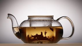 Leaves of green tea are brewed in teapot, white background. Leaves of green leaf tea are brewed in glass teapot, boiling water is poured from kettle in stock video