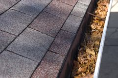 Leaves in Gutter, Home Maintenance and Repair. Time to clean out the leaves out of the gutters and do that work around the house for home maintenance and repair Stock Photos