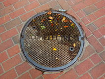 Leaves on a manhold cover. Autumn leaves on a manhole cover in Martha's Vineyard, Massachusetts, USA Royalty Free Stock Photo