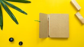 Leaves nature and notebook with woodblock  on yellow background. Business concept stock photos