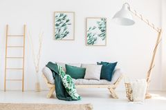 Classic living room with lamp. Leaves painting above sofa with green pillows and blanket in classic living room with designer lamp Stock Photo