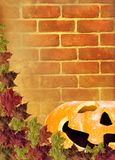 Leaves with pumpkin on wall Brick brown background Stock Photos