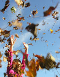 Leaves in the wind. A girl with arms in air with leaves all around Stock Photos