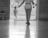 Leaving. Black and white picture of little boy and older child walking thru door to outside Stock Images