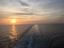 Leaving it all behind. Ocean sunset, clouds and ship wake Royalty Free Stock Photo