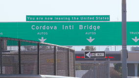 Leaving America. Traffic passes with the Cordova International Bridge in the background stock footage