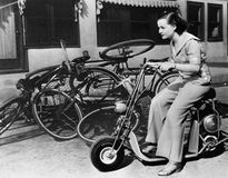 Leaving bicycles in the dust, a young woman fancies a miniature motorbike Stock Images