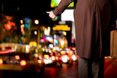 Leaving the city. A hitchhiker with an old suitcase is waiting on a sidewalk as night city traffic flows by Stock Image