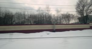 Leaving the city by train, view from the window. View from the window of a train traveling through the city in winter. Passing by the houses and industrial stock video footage