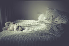 Leaving dog doll lonely alone on the bed in the morning. Stock Image