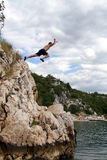 Leaving Ground. A young man jumps from a cliff into the sea Royalty Free Stock Photo