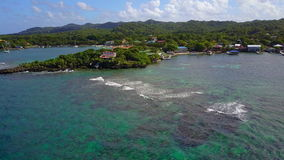 Leaving island coast. Aerial pulling away of island coast passing turquoise waters and fishing boat stock footage