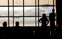 Leaving on a Jet Plane. Family looking out the window at the airport Royalty Free Stock Photos