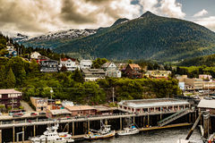 Leaving Ketchikan. Ketchikan, AK, USA - May 24, 2016: View of homes, hills, clouds and docksde commercial properties in Ktchikan Alaska royalty free stock photo