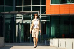 Leaving the Office. Professional young businesswoman leaving a modern office building stock photos