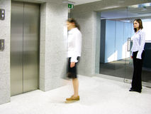 Leaving the office. Long exposure shot of a woman leaving the office towards elevators (motion blurred). Her colleague is standing still in the background royalty free stock image