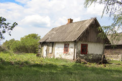 Leaving a reality - life goes on. Old abandoned farmhouse near blooming trees against the bright spring sky - life goes on.n«If time exists in nature, then it royalty free stock photo