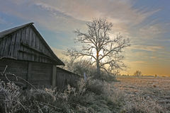 Leaving the reality in the rural outback. Abandoned barn in rural outback to the winter landscape of the rising sun stock photos