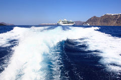 Leaving Santorini. Blue waters of the ionian sea and the cruise ship in the caldera of the volcanic greek island of santorini Royalty Free Stock Photo