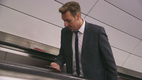 Leaving the Subway. Businessman using his smartphone as he makes his way out from the subway platform usin the escalator. He is wearing a formal suit and has a stock video