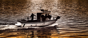 Leaving at sunset. Fishing boat leaving at sunset Royalty Free Stock Photography