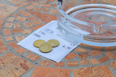 Leaving a tip. Coins on a bar receipt of drinks, indicating leaving a tip for the waiter/waitress stock photography