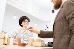 Leaving tip for friendly barista. Close-up of bearded men in jacket leaving tip for friendly barista while buying coffee and snacks in coffee shop stock photo
