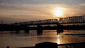 Leaving train across the river at sunset. Sunset background. bridge over water. . river water reflection. rail road street. transportation traffic 1920x1080 stock footage