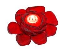 Leavs rojos de las rosas y vela que brilla intensamente. Foto de archivo libre de regalías