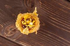 Lebanese baklava nest on brown wood. One whole sweet lebanese baklava piece bird nest variety copyspace flatlay on brown wood royalty free stock photos