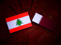 Lebanese flag with Qatari flag on a tree stump isolated. Lebanese flag with Qatari flag on a tree stump Stock Photography