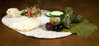 Lebanese Mezza. Traditional Lebanese Mezza of hummas, tabouleh, dolma, fatayee and spiced olives on flatbread Stock Photos