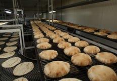 Lebanese pita bread on conveyor Stock Photos