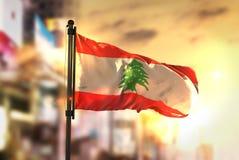Lebanon Flag Against City Blurred Background At Sunrise Backlight. Sky stock photos