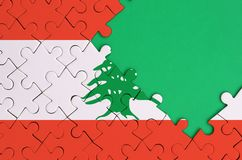Lebanon flag is depicted on a completed jigsaw puzzle with free green copy space on the right side.  stock illustration