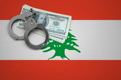 Lebanon flag with handcuffs and a bundle of dollars. The concept of breaking the law and thieves crimes.  royalty free illustration