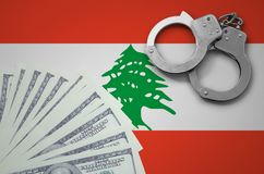 Lebanon flag with handcuffs and a bundle of dollars. The concept of illegal banking operations in US currency.  royalty free illustration