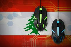 Lebanon flag and two mice with backlight. Online cooperative games. Cyber sport team. Lebanon flag and two modern computer mice with backlight. The concept of vector illustration