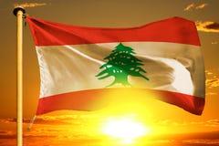 Lebanon flag weaving on the beautiful orange sunset with clouds background. Lebanon flag weaving on the beautiful orange sunset background stock photos
