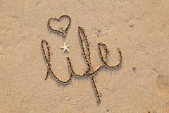 Leben geschrieben in Sand mit Innerem Stockbild