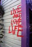 Leben Sie und lieben Sie das Leben (Nimbin-Graffiti) Stockbilder