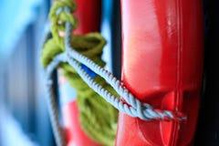 Lebenboje in der roten Farbe mit grauem Seilkabel auf Seeschiffsboot auf unscharfem blauem Hintergrund, Rettungsringsicherheitsre lizenzfreie stockfotografie