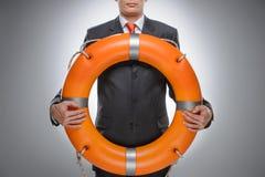 Lebenboje für Ihr Geschäft. Geschäftsmann, der ein Rettungsgürtel whi hält Lizenzfreies Stockbild
